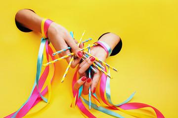 Obraz Cukierkowy manicure w stylu pin up. Dłonie z pomalowanymi paznokciami, udekorowane kolorowymi wstążkami na żółtym tle. - fototapety do salonu
