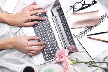 Obraz Kobieta pracuje on line. Kobieta pisze na komputerze leżąc na łóżku. - fototapety do salonu