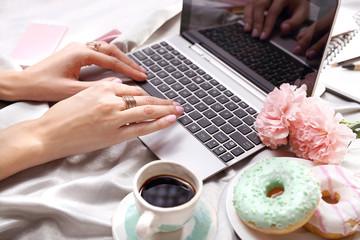 Fototapeta Praca on line. Kobieta pisze na komputerze leżąc na łóżku. obraz