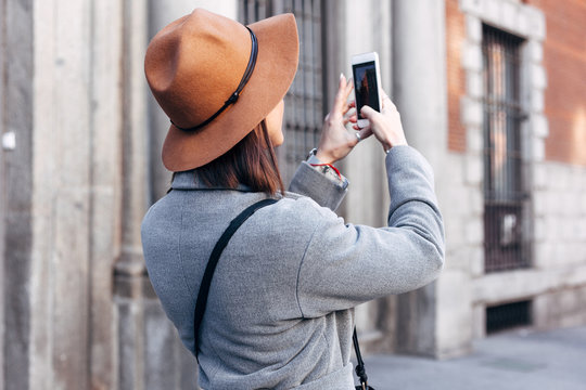 Beautiful woman are making photos with smartphone on the street