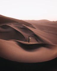 Man holding light in the middle of desert dunes