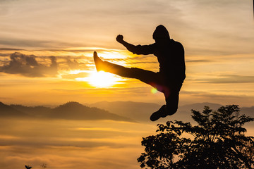 Silhouette of happy man jumping at sunset or sunrise time