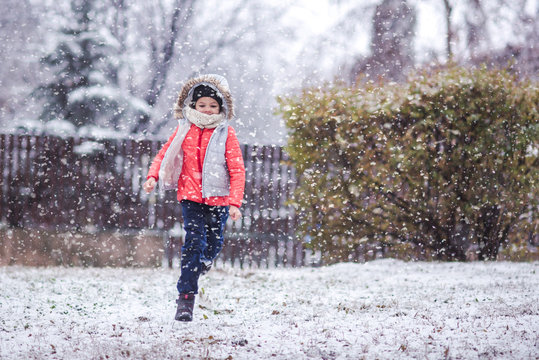 Happy young girl running in a park enjoying the falling snow