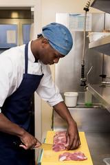 Kitchen worker slicing meat