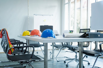 Colorful helmet and file folder on white table in meeting room.