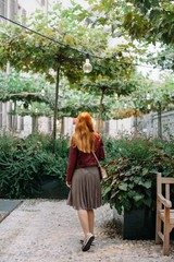 Back view portrait of redhead girl walking by the garden