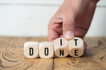 "Hand turns two cubes, changing the word ""do it"" to ""done"""