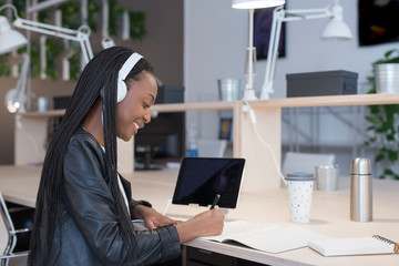 Cheerful young woman working in headphones