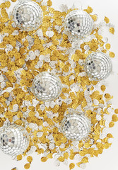 Mirrored disco balls on gold and silver party confetti.