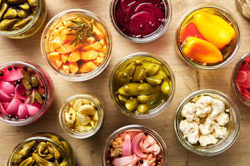 Opened homemade pickles of different vegetables in jars.