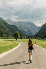Young woman walking on the road heading through the beautiful landscape alpine valley.