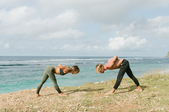 Two persons man and woman wearing sporty clothes doing yoga together on the beach practice,  with ocean view