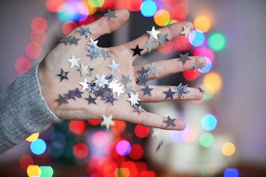 Hand covered in silver star confetti