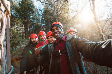 A group of friends take a selfie before going on an outdoor zip lining adventure