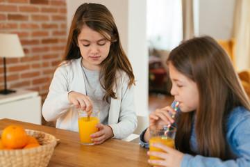 Girls drinking orange juice
