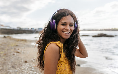 Young woman listening to music with headphones on the beach at s