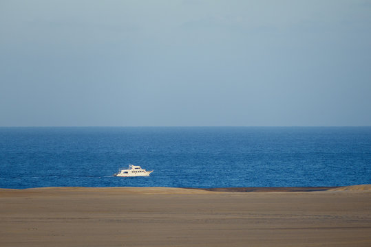 White distant cruise ship sailing on the Red Sea with copyspace