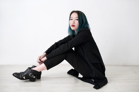 Cool asian woman sitting on a floor