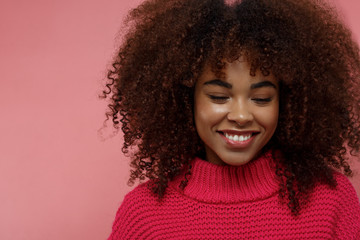 Portrait of a young African American afro woman in pink studio smiling looking down