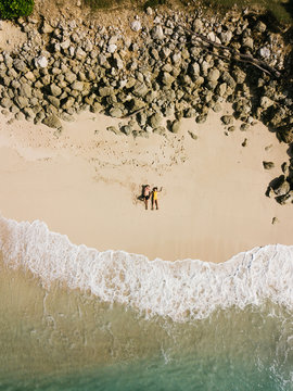 A couple yang women and man lie on the beach in the day light close to waves of the clean blue ocean water holding hands together