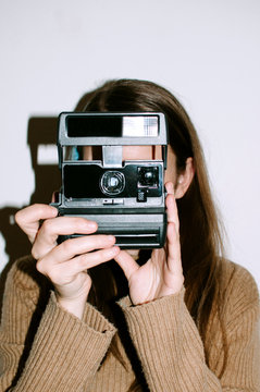 Young woman with vintage polaroid camera