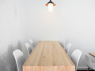 Real wood table with white chairs in a modern luxury restaurant focusing on minimalist architecture.