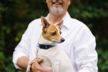 Happy, Elderly Man Holding Small Dog