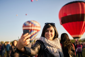 Young woman taking a selfie at a balloon festival