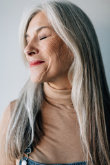 Portrait of a smiling senior woman with grey long hair.