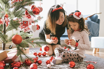 A cute  girl and her mother decorating christmas tree at home
