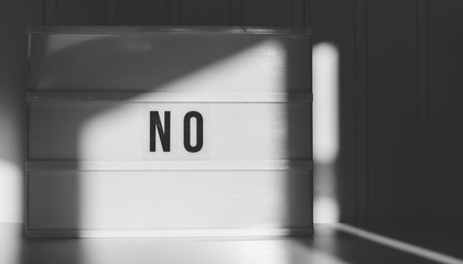 Black and white image of the word No spelled out on a light box.