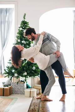 Couple in love dancing in front of Christmas tree at home.