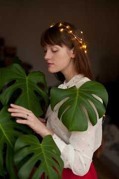 Portrait of young woman wearing a crown of lights among leaves of monstera