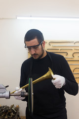 Man fixing trumpets in his repair workshop
