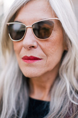 Closeup portrait of a mature woman with grey hair   wearing sunglasses.