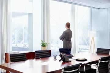 Businessman Looking Through Window In Office