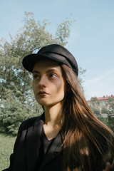 portrait of a beautiful girl in a black ball cap on Sunny street