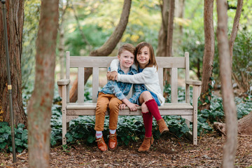 Adorable and stylish siblings sitting on a bench together