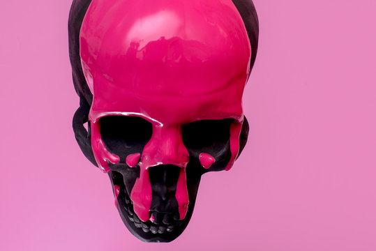 Black Skull with Pink paint running down it against a pink background