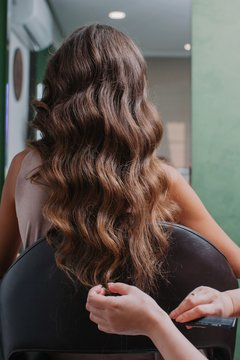 Closeup view of curly long hair and crop hands making the hairstyle