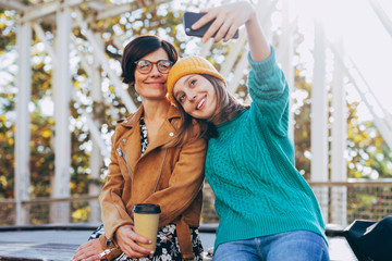 Mother and her daughter taking a selfie on the street in autumn.