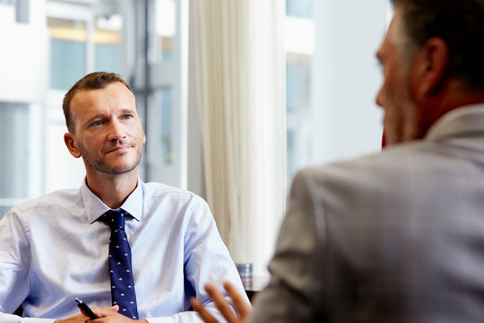 Businessman Listening To Colleague In Office