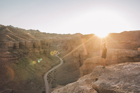 sporty woman on the edge of a canyon enjoying sunset