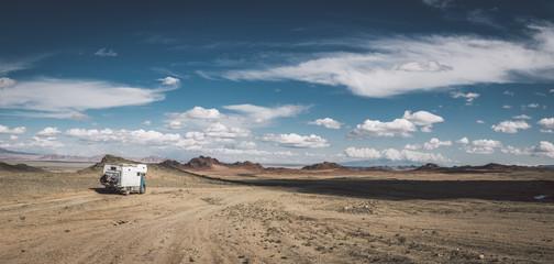 panorama shot of a camping truck in mongolian desert