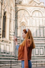 Side view portrait of redhead girl taking picture of Duomo in Florence