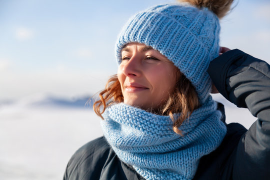 Fashion lifestyle portrait of young trendy woman dressed in warm stylish clothes  enjoy winter and smiling in the  winter.  portrait of joyful woman, in the background white snow and frozen mountains