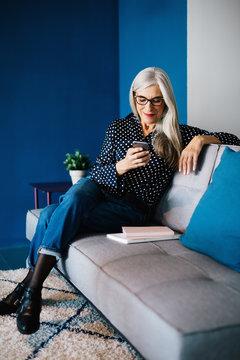 Portrait of a senior businesswoman sitting on sofa using her phone.
