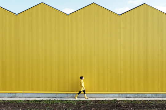 Woman walking by yellow building