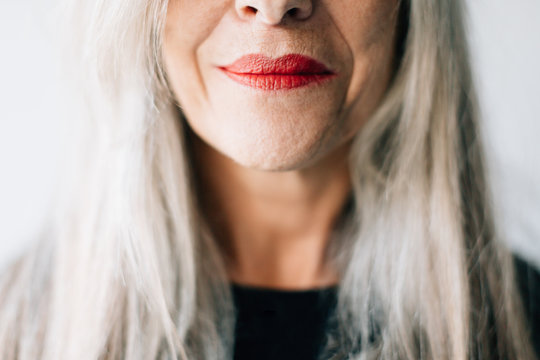 Close up of senior woman with gray hair and red lipstick
