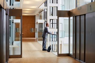 Thoughtful Businessman Standing In Corridor